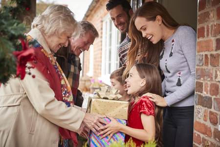 Grandparents Being Greeted By Family As They Arrive For Visit On Christmas Day With Gifts 写真素材