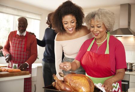 Les membres de la famille seniors et jeunes adultes de race mixte parlent dans la cuisine tout en préparant le dîner de Noël ensemble, en gros plan
