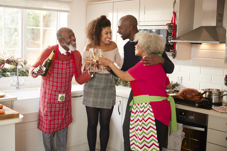 Multi-ethnic adult family embrace and make a toast with champagne to celebrate on Christmas Day while preparing dinner together in the kitchen Stock Photo