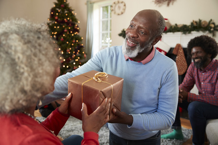 Senior Couple Exchanging Gifts As They Celebrate Christmas At Home With Family Stock Photo