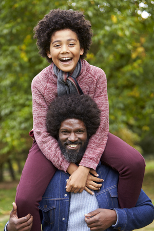 Black middle aged man carrying his son on his shoulders in the park, both smiling to camera, close up Stock Photo