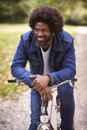 Black middle aged man sitting on a bike in  a park, leaning on the handlebars smiling, front view, close up