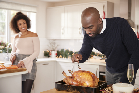 Young adult mixed race couple preparing Christmas dinner together at home, man basting roast turkey in the foreground, front view, close up