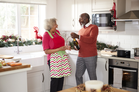 Senior black couple opening champagne and laughing together in the kitchen while preparing dinner on Christmas Day, selective focus