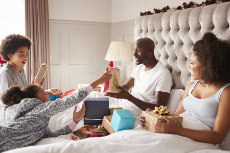 Young mixed race family sitting on parents� bed giving each other gifts on Christmas morning, close up Stock Photo