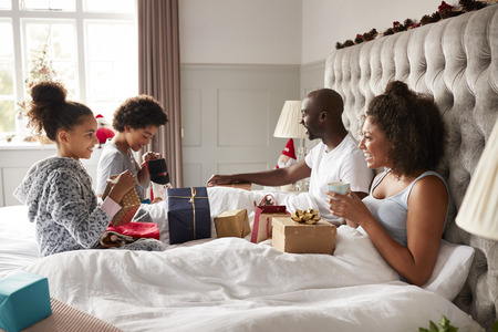 Young kids opening gifts on parents� bed on Christmas morning while their parents sit up in bed watching, side view