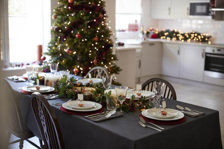 Christmas table setting with bauble name card holders arranged on plates and green and red decorations with Christmas tree and kitchen in the background Stock Photo