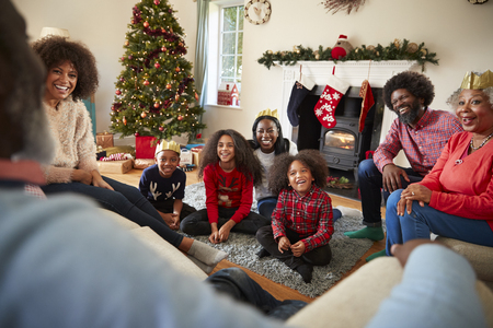 Multi Generation Family Sitting In Lounge At Home On Christmas Day Stock Photo