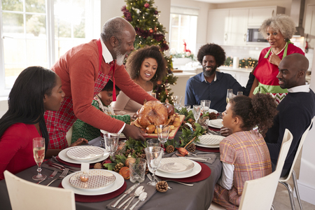 Grandfather bringing the roast turkey to the dinner table during a multi generation, mixed race family Christmas celebration, elevated view