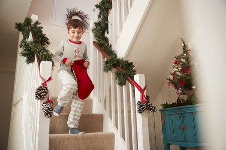Excited Boy Wearing Pajamas Running Down Stairs Holding Stocking On Christmas Morning Banco de Imagens