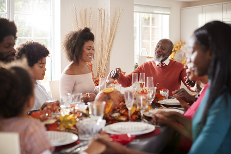 Multi generation mixed race family holding hands and saying grace before eating at their Thanksgiving dinner table, selective focus Stock Photo