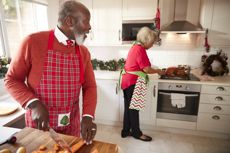 Mature black couple preparing Christmas dinner, man chopping vegetables in the foreground, turning to his partner who is preparing the turkey
