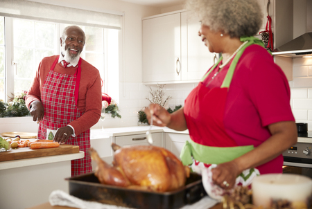 Senior black woman preparing a roast turkey for Christmas dinner turns to talk to her husband, chopping vegetables in the background, close up