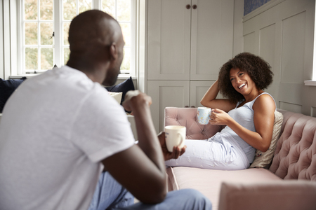 Young adult black woman sitting on a couch drinking coffee smiling at her partner, selective focus