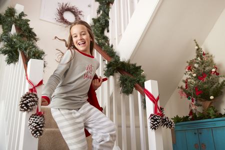 Excited Girl Wearing Pajamas Running Down Stairs Holding Stocking On Christmas Morning Stock Photo