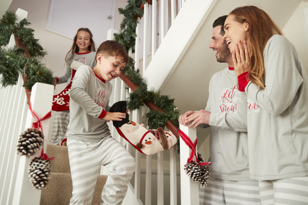 Parents Greeting Excited Children Wearing Pajamas Running Down Stairs Holding Stockings On Christmas Morning