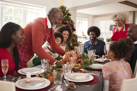 Grandfather bringing the roast turkey to the dinner table during a multi generation, mixed race family Christmas celebration, close up Stock Photo