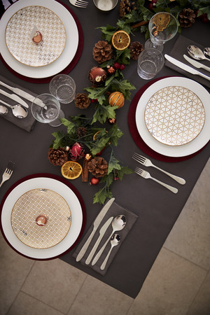Christmas table setting with baubles arranged on plates and green and red table decorations, overhead view, vertical