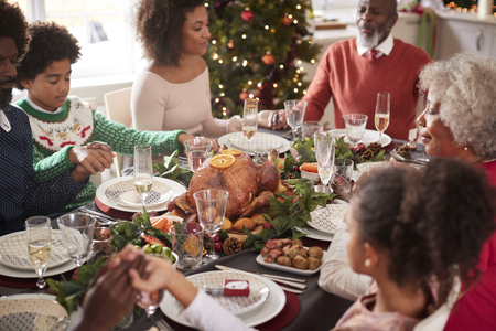Multi generation mixed race family sitting at Christmas dinner table holding hands and saying grace, elevated view Stock Photo