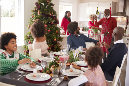 Mixed race, multi generation family gathering in dining room to sit down for Christmas dinner, grandfather holding champagne bottle