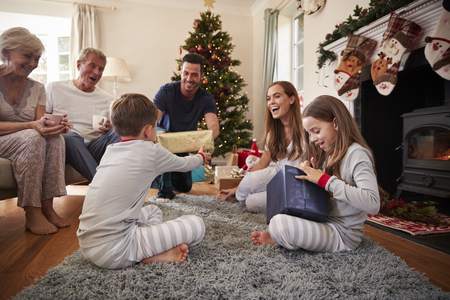 Three Generation Family Wearing Pajamas In Lounge At Home Opening Gifts On Christmas Day