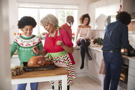 Mixed race, multi generation family talking in the kitchen while they prepare Christmas dinner together