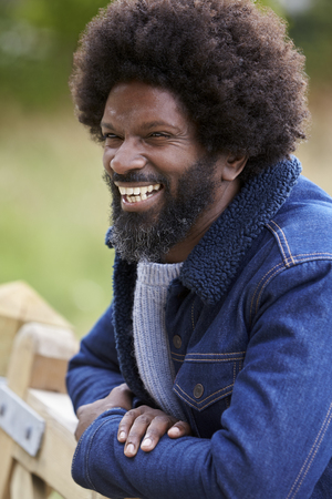 Black man leaning on a wooden fence in the countryside laughing, close up