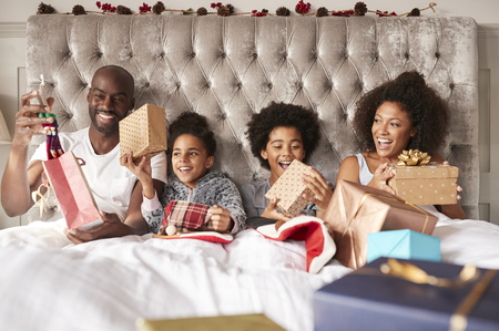 Young mixed race family sitting up in bed together holding presents on Christmas morning, front view, close up Reklamní fotografie