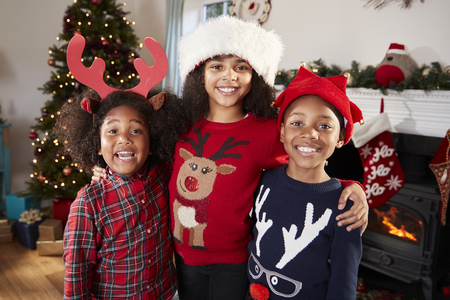 Portrait Of Children Wearing Festive Jumpers And Hats Celebrating Christmas At Home Together