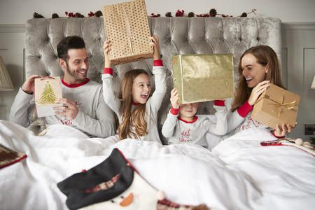 Excited Family In Bed At Home Opening Gifts On Christmas Day Stockfoto - 115490435