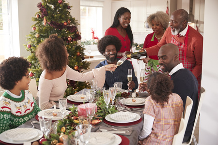 Grandfather pouring champagne at the dinner table during a multi generation, mixed race family Christmas celebration