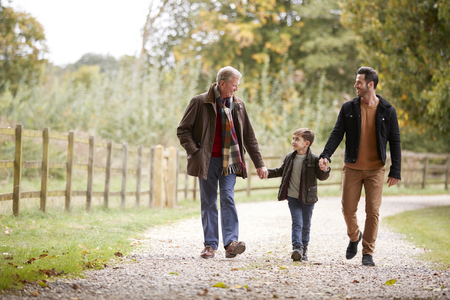 Grandfather With Son And Grandson On Autumn Walk In Countryside Together Stock Photo