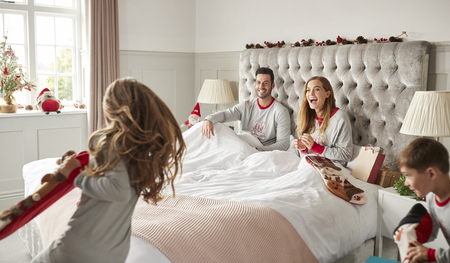 Excited Children Running Into Parents Bedroom At Home With Stockings As Family Open Gifts On Christmas Day Stock Photo