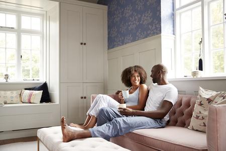 Junges schwarzes Paar sitzt zusammen auf der Couch im Wohnzimmer, trinkt Kaffee und spricht morgens, niedriger Winkel, volle Länge Standard-Bild