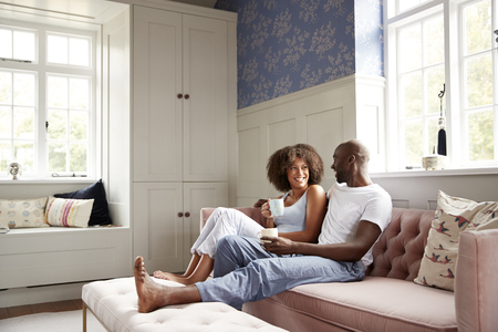 Young black couple sitting together on couch in living room drinking coffee and talking in the morning, low angle, full length