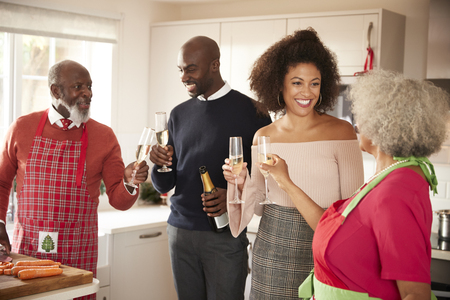 Mixed race senior and young adult family raise champagne glasses to celebrate, while preparing Christmas dinner together in the kitchen, close up Stock Photo