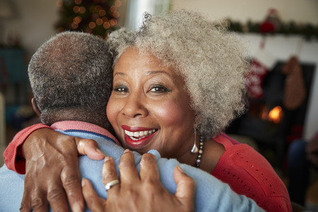 Portrait Of Senior Couple Hugging As They Celebrate Christmas At Home Together Stock Photo