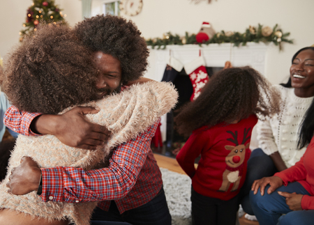 Couple Hugging As They Exchange Gifts At Multi Generation Family Christmas At Home