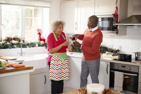 Senior black man pouring champagne for his partner in the kitchen while preparing dinner on Christmas Day, selective focus