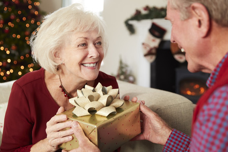 Excited Mother Receiving Christmas Gift From Daughter At Home