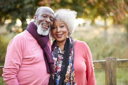 Portrait Of Senior Couple On Autumn Walk In Countryside Together