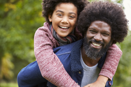 Black man piggybacking his pre-teen son in the park, both smiling to camera, close up