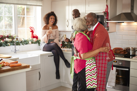 Multi-ethnic adult family celebrating  with champagne, talking and dancing in the kitchen while preparing dinner on Christmas Day