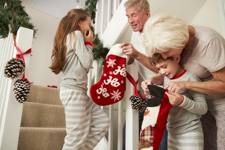 Grandparents Greeting Excited Grandchildren Wearing Pajamas Running Down Stairs Holding Stockings On Christmas Morning