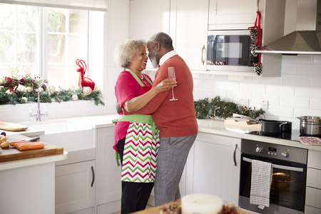 Happy mature black couple holding champagne glasses, laughing and embracing in the kitchen while preparing meal on Christmas morning, side view
