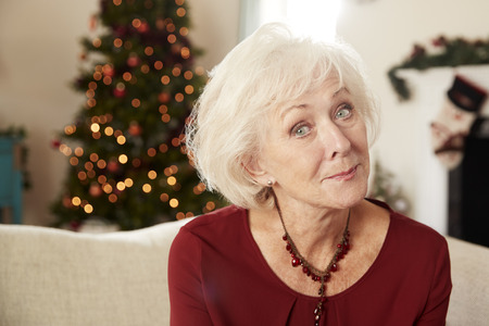 Portrait Of Senior Woman Sitting On Sofa In Lounge At Home On Christmas Day