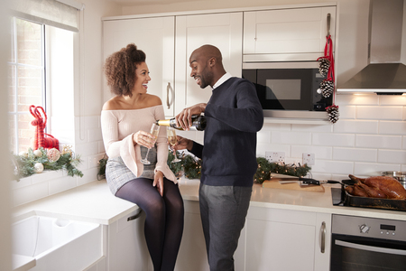 Young black man pouring champagne for his partner in the kitchen while they prepare Christmas dinner Stock Photo