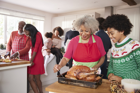 Mixed race, multi generation family gathered in kitchen before Christmas dinner, grandmother and grandson preparing roast turkey in foreground Stock Photo
