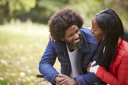 Black couple embracing and looking at each other smiling in a park, close up
