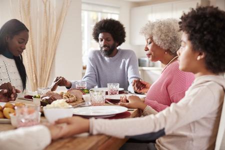 Famiglia di razza mista multigenerazionale che si tiene per mano e dice grazia prima di mangiare la cena della domenica, messa a fuoco selettiva